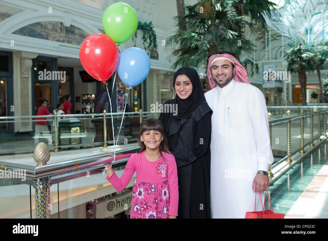 La familia árabe en el shopping mall, Chica sujetando globos. Imagen De Stock