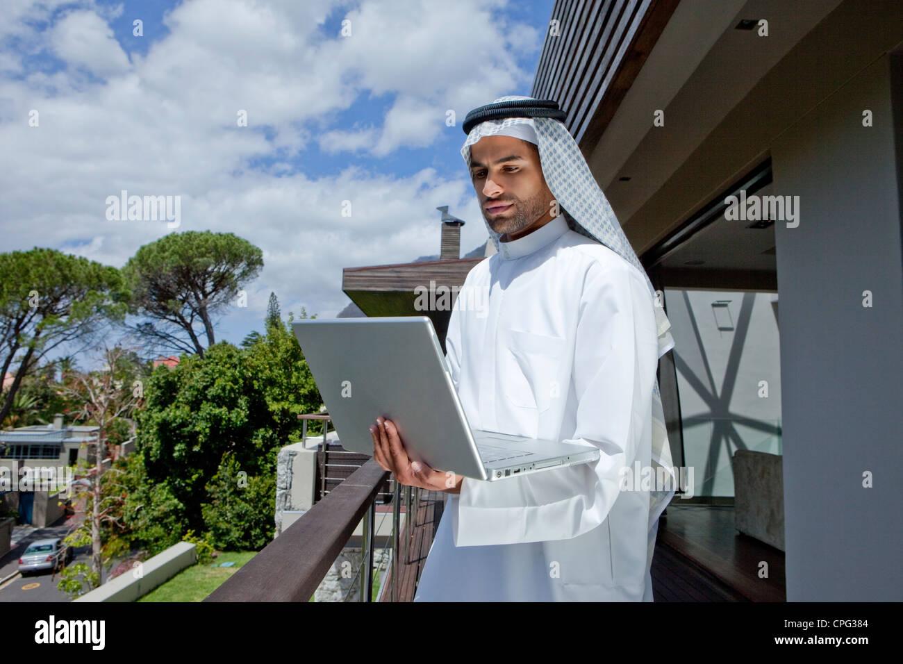 Hombre árabe con laptop, parado por el balcón. Imagen De Stock