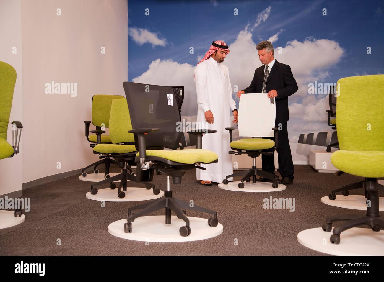 Vendedor ayudando al hombre árabe para compras de sillas de oficina en tienda de muebles. Foto de stock