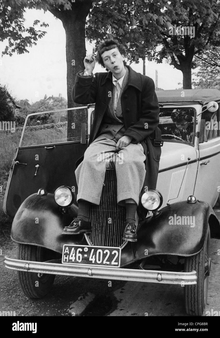 Mujeres, personas y 1950, joven en la ropa de los hombres se sienta sobre el capó de un coche, Alemania, 1952 Imagen De Stock
