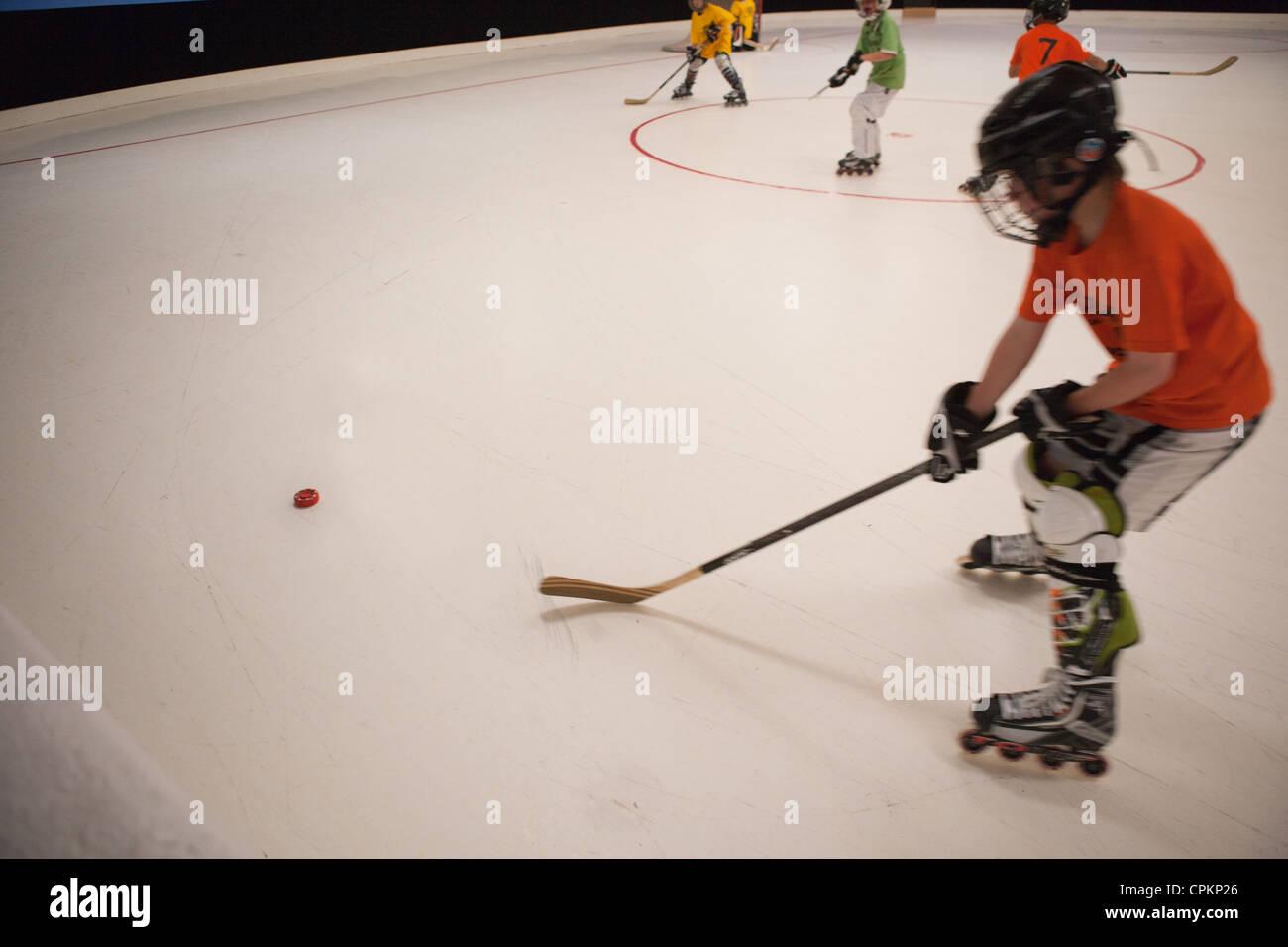Jugador de hockey sobre hielo, patinaje sobre hielo en la juventud, con el objetivo de liga de hockey puck. Imagen De Stock