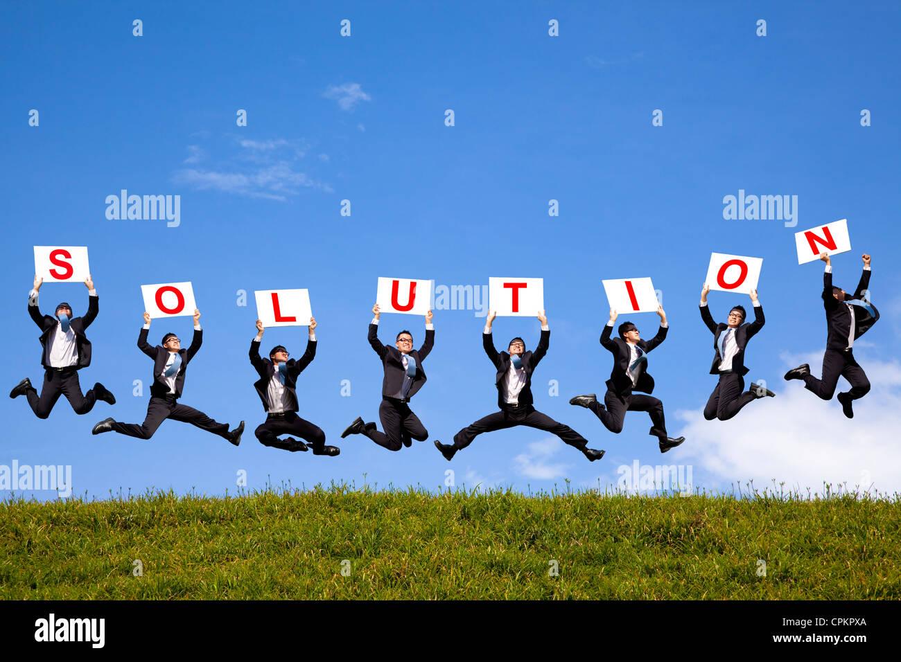 Empresario feliz celebración texto de solución y saltar sobre el campo verde Imagen De Stock