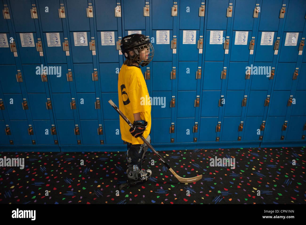 Niño de nueve años de pie en frente de armarios, preparándose para jugar hockey. Imagen De Stock