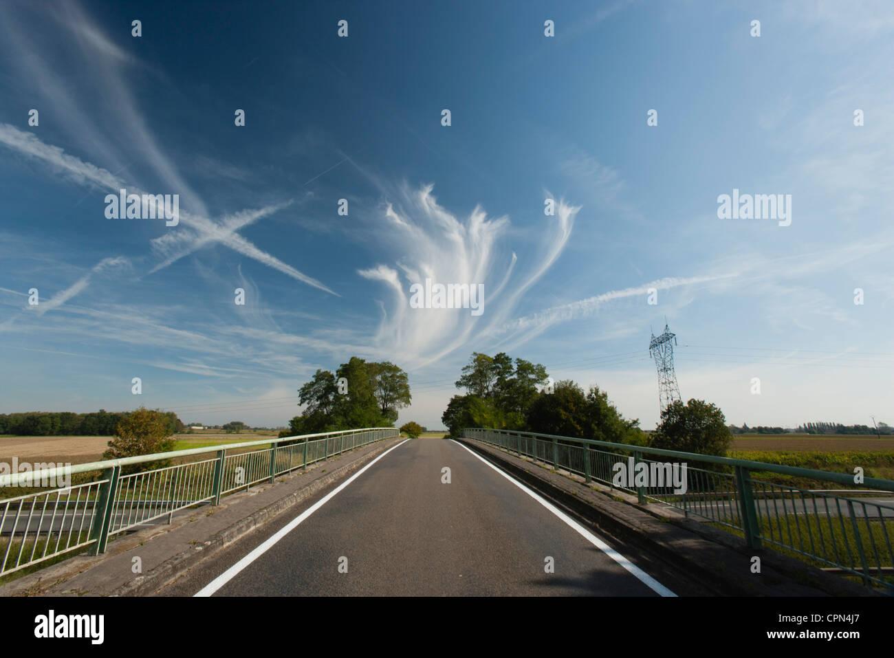 Whispy nubes de vapor y senderos en el cielo sobre el puente Imagen De Stock