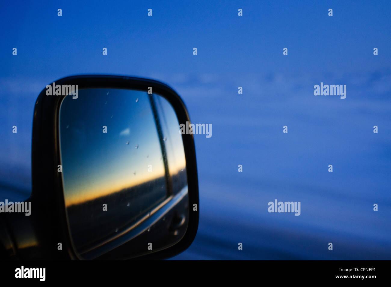 Puesta de sol reflejada en coche retrovisor Foto de stock