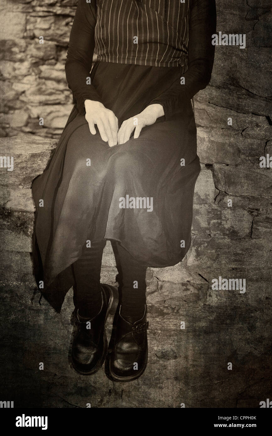 Una mujer sentada sobre un antiguo muro de piedra en la antigua VINTAGE DRESS Imagen De Stock