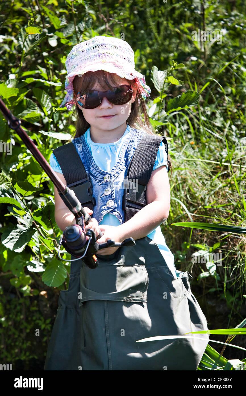 Niña de pescar en el lago en verano Imagen De Stock