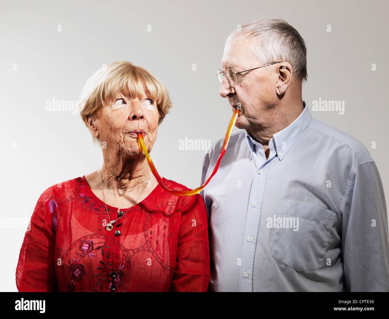 Senior pareja compartiendo dulces contra el fondo blanco. Imagen De Stock