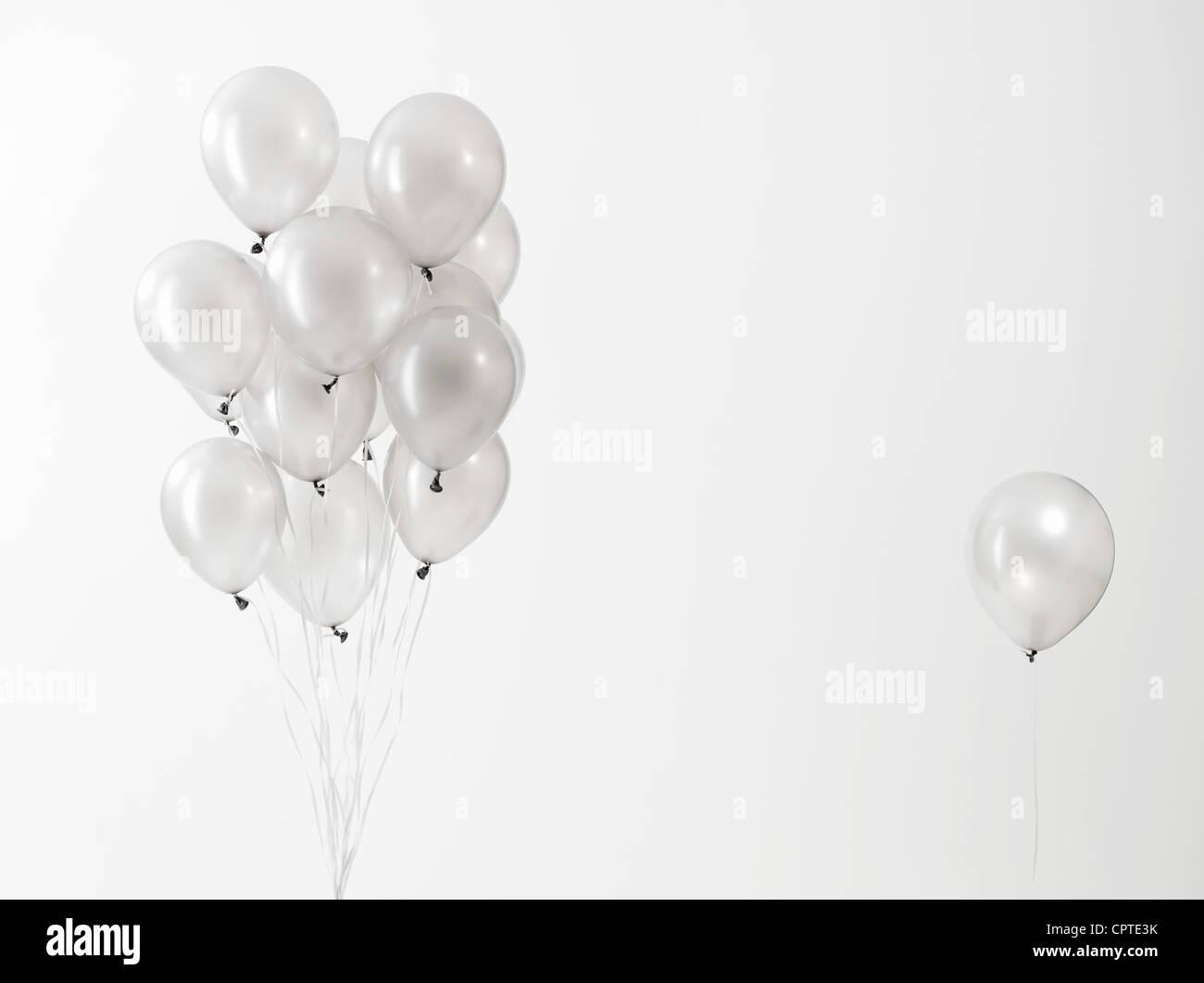 Globos plateados flotando contra fondo blanco. Imagen De Stock