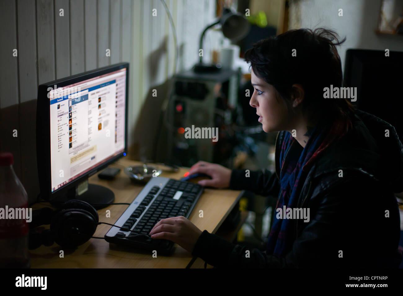 Mujer joven revisando su facebook en el equipo. Imagen De Stock