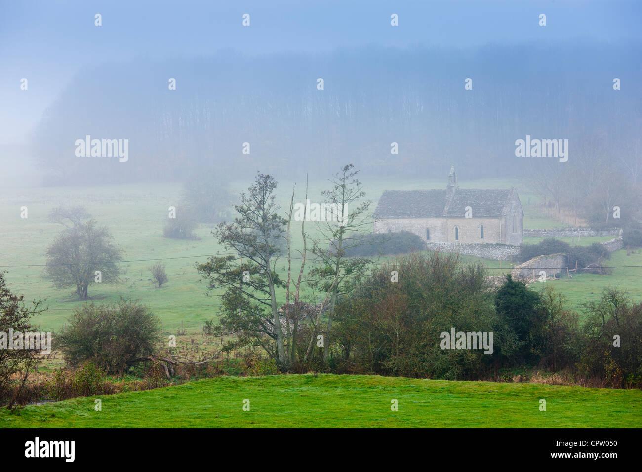 Misty escena y la iglesia de St Oswald, una capilla remota en un campo, en Widford cerca de Burford en Cotswolds, Oxfordshire, REINO UNIDO Foto de stock