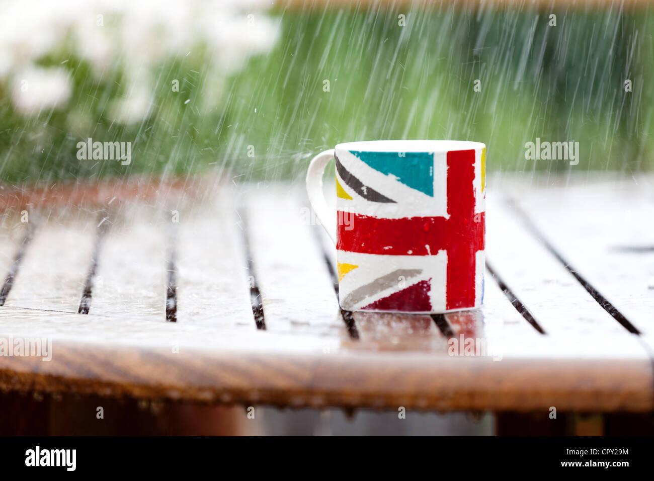 Una union jack marcada mug abandonado en una mesa fuera en una tormenta de lluvia. Imagen De Stock