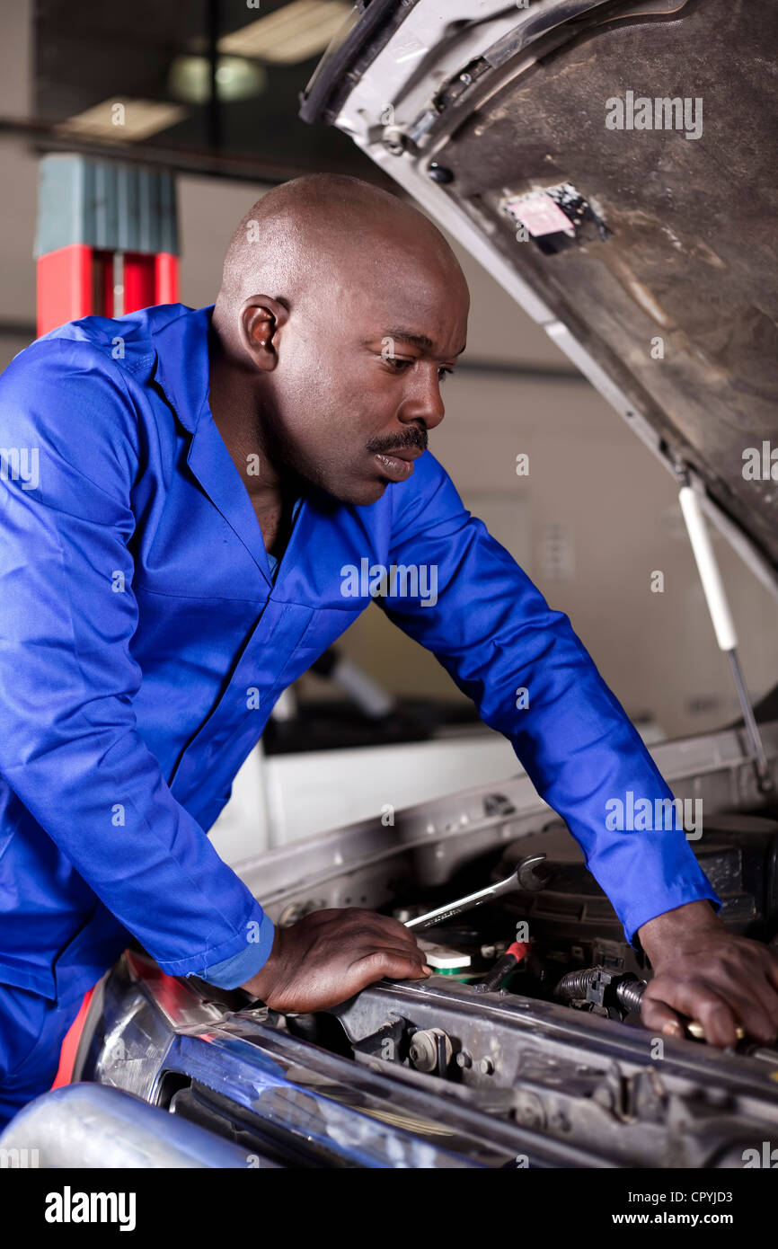 Hombre africano trabajando en un motor de automóvil Foto de stock