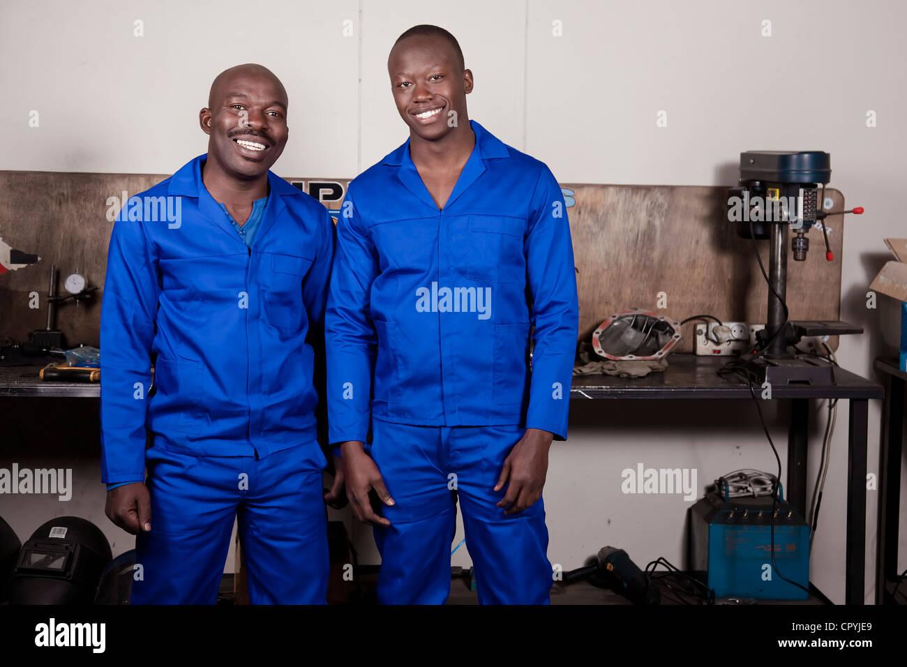 Dos africanos mecánica en un taller permanente sonriendo a la cámara Foto de stock