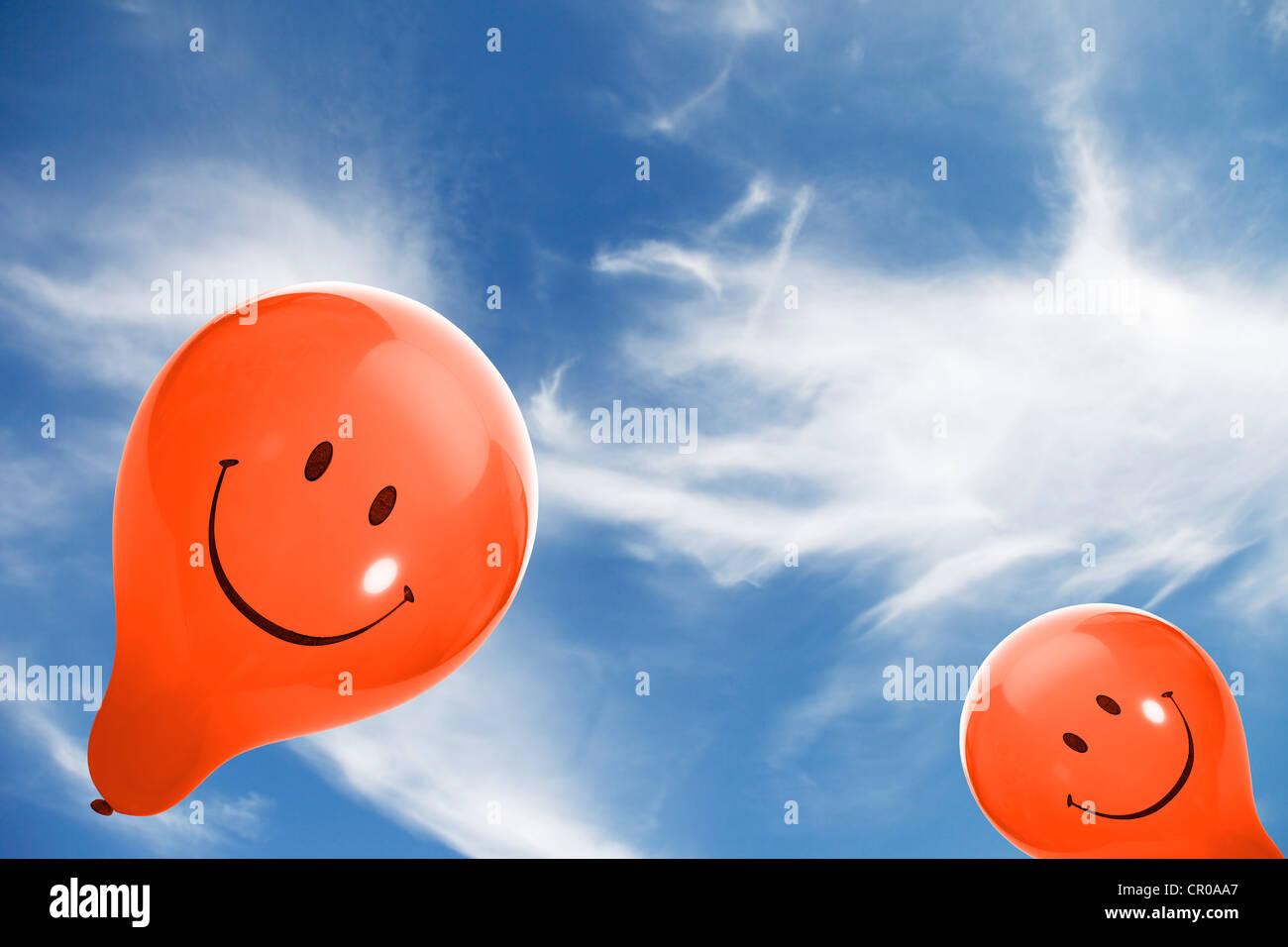 Dos globos smiley naranja contra un cielo azul con nubes Imagen De Stock