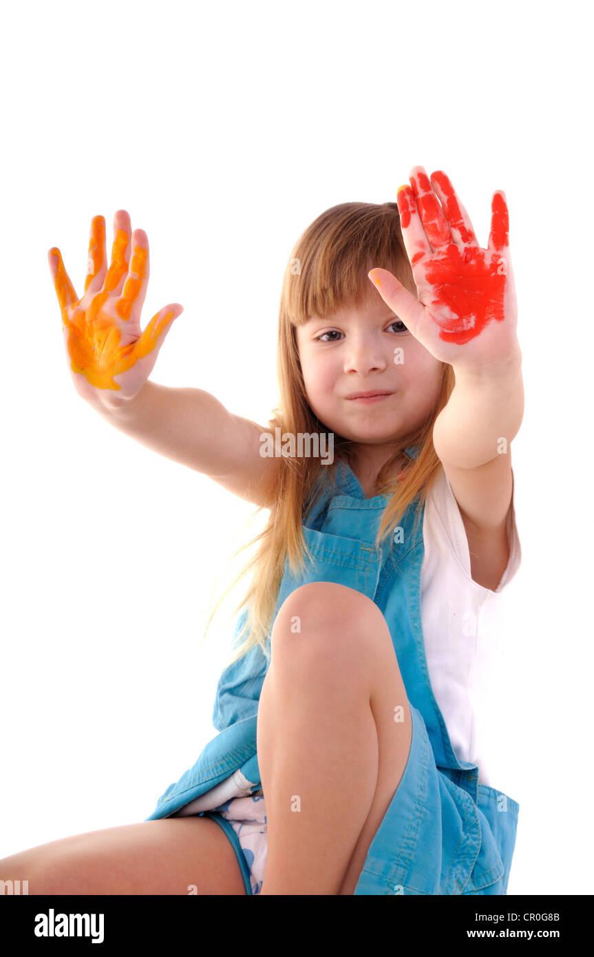 Pequeña Belleza juguetona chica con muchas manos de color sobre fondo blanco. Foto de stock