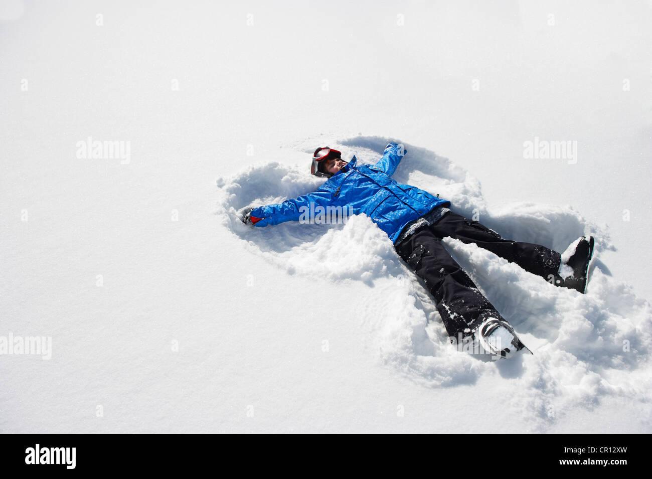 Boy haciendo ángel de nieve Imagen De Stock