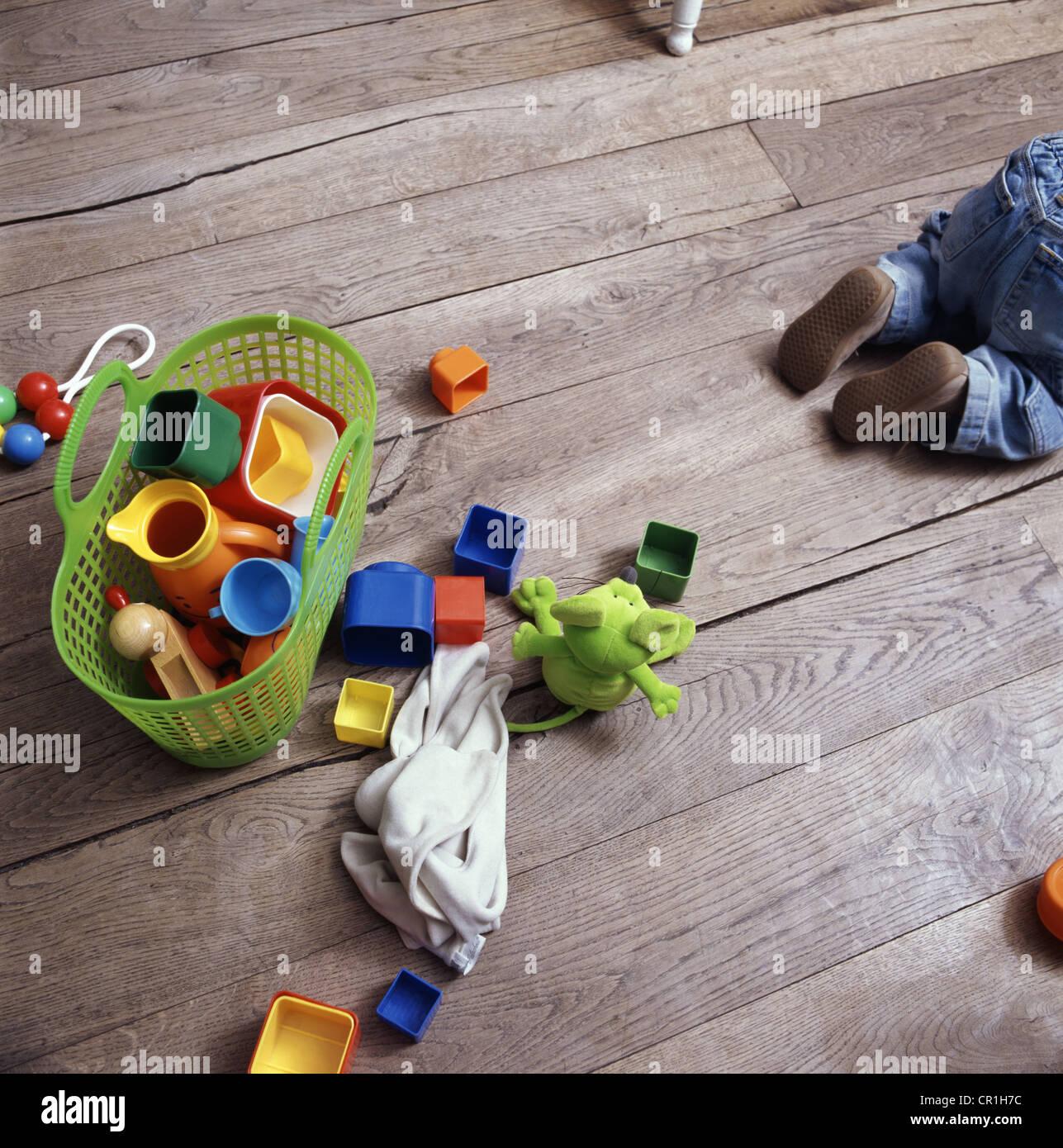 Bebés juguetes sobre un piso de madera Foto de stock