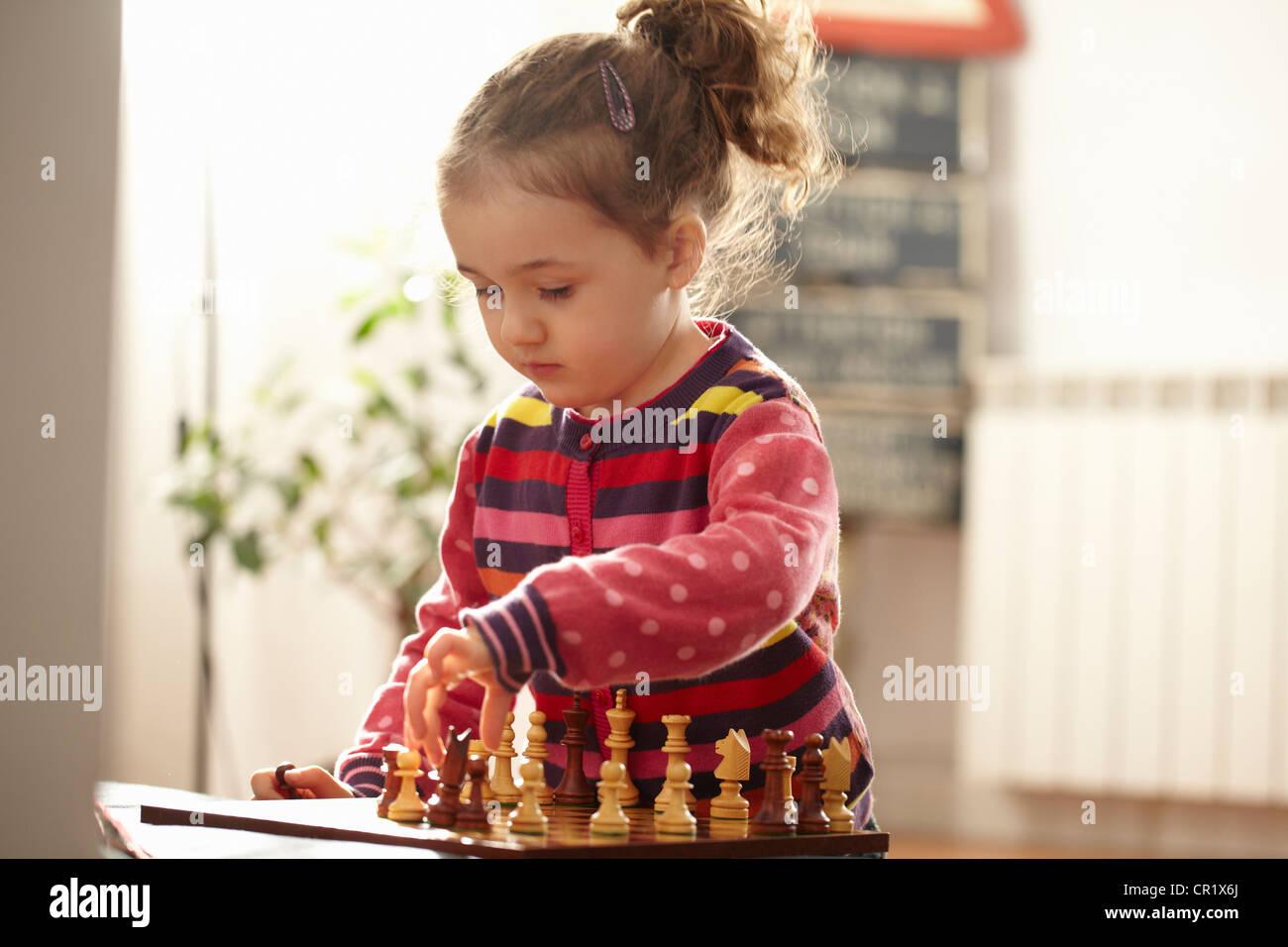 Chica jugando ajedrez en interiores Imagen De Stock