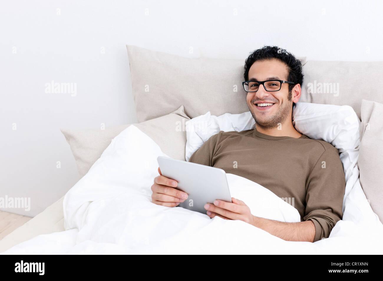 Hombre utilizando tablet PC en la cama Imagen De Stock