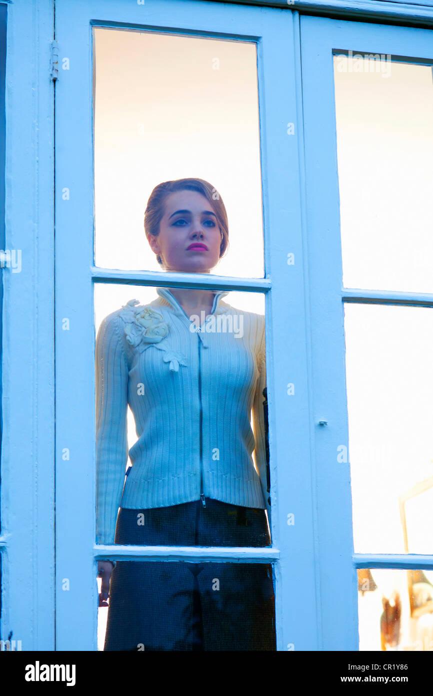 Mujer mirando afuera de la puerta de vidrio Imagen De Stock
