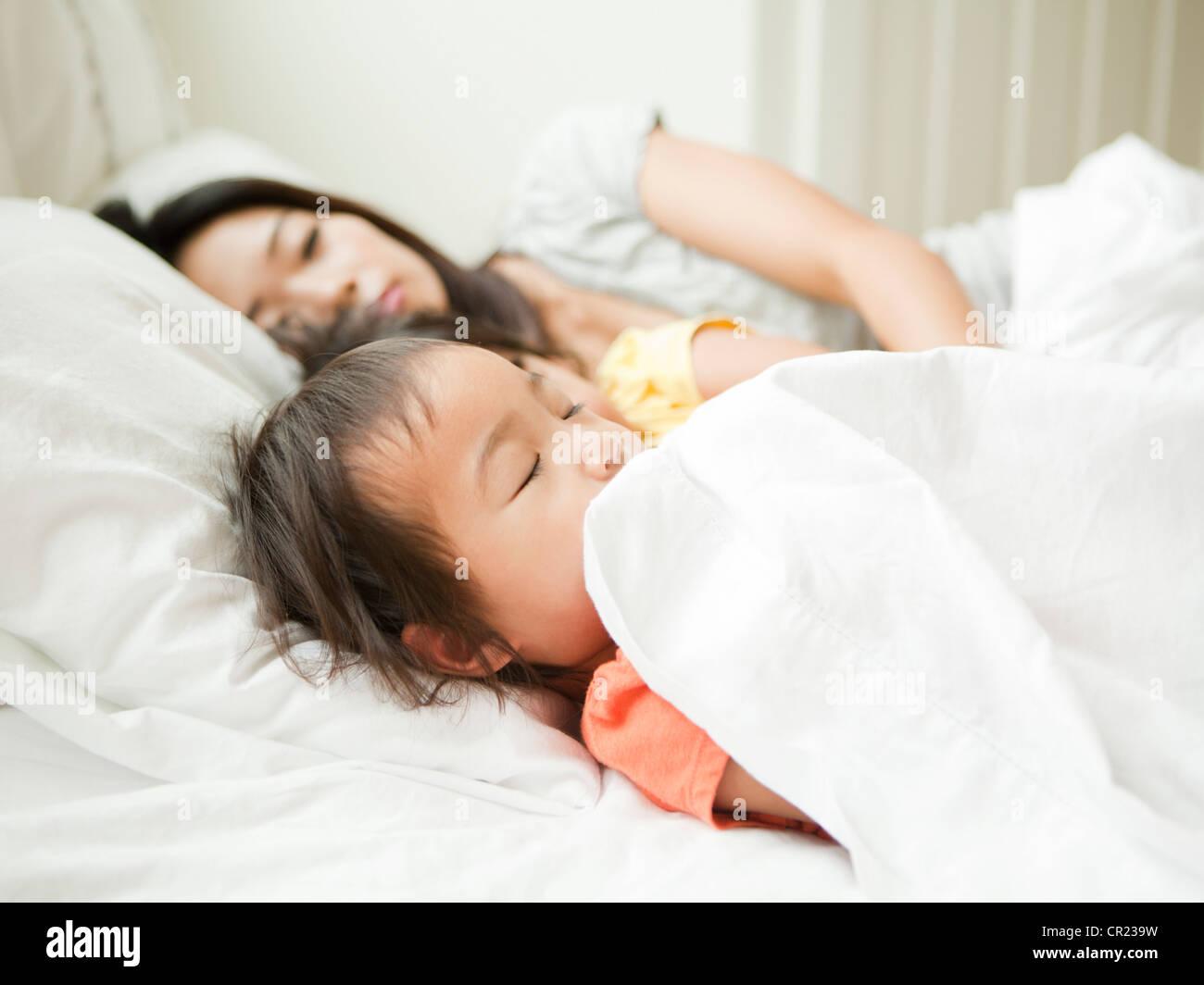 Madre con sus hijas (2-3, 4-5) durmiendo juntos Imagen De Stock