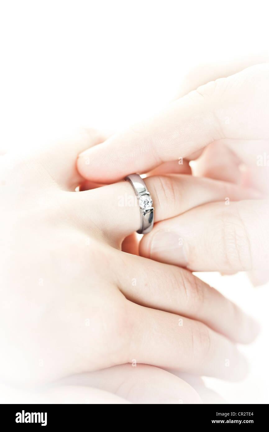 61061c02b26b Primer plano de Manos colocando el anillo de compromiso en el dedo Imagen  De Stock
