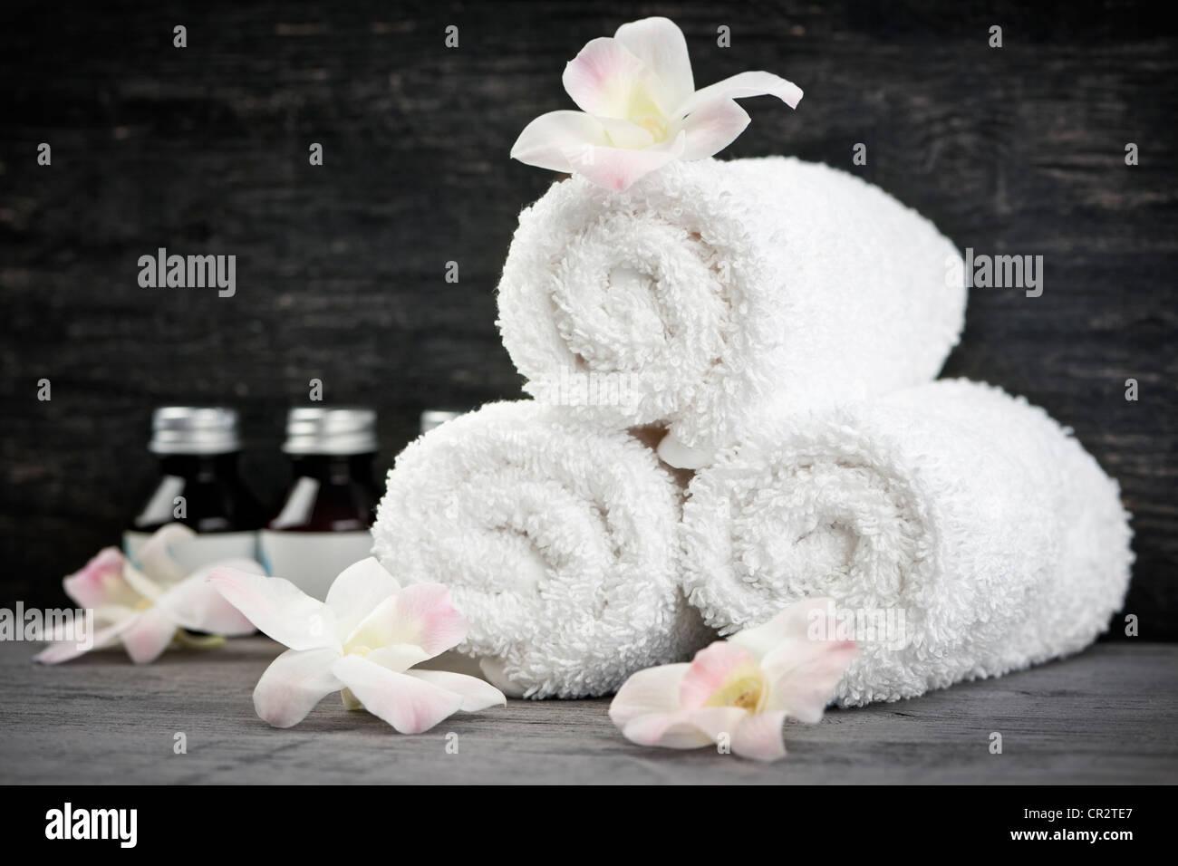 Blanco toallas enrolladas con productos para el cuidado del cuerpo en el spa Imagen De Stock
