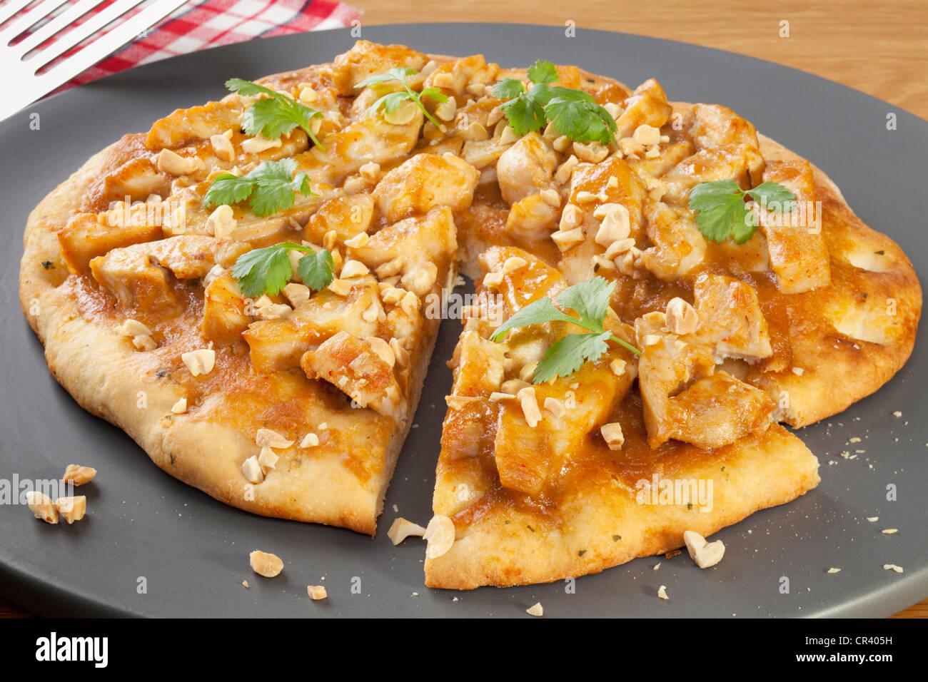 La Pizza de pollo Satay, rematada con cilantro y maní tostado. Imagen De Stock