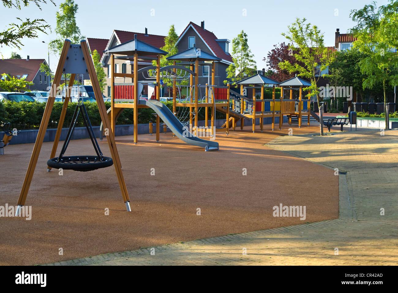 c4a0bf63b Parque infantil público con coloridos de madera de construcción de  escalada, columpio, toboganes y piso de caucho para jugar de forma segura