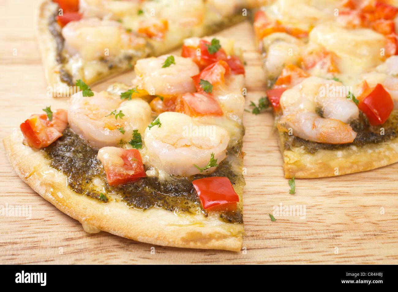 Base crujiente pizza rematada con gambas, pimiento rojo, mozzarella y pesto de albahaca. Imagen De Stock