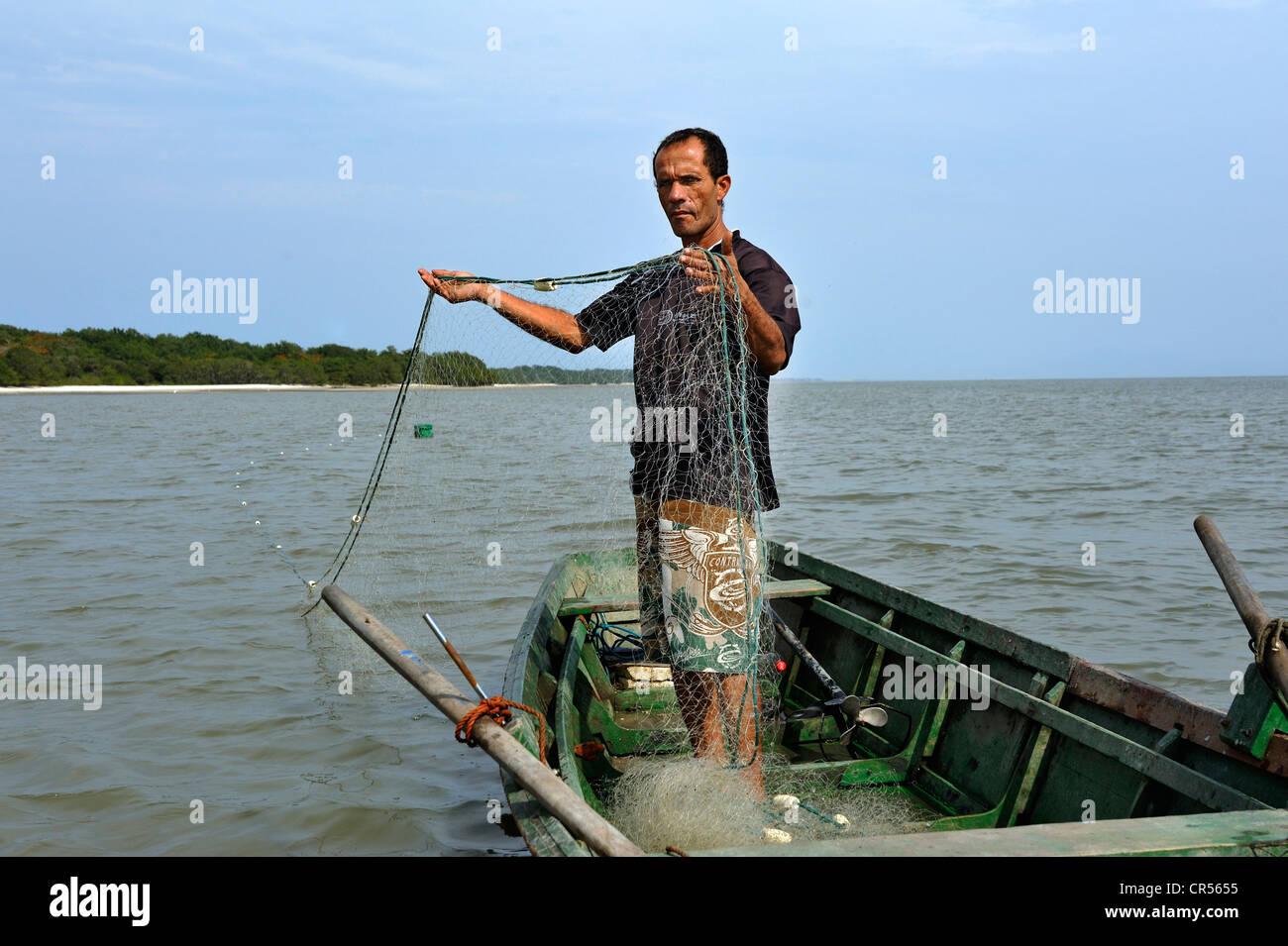 Pescador en un pequeño bote con una red en Sepitiba Bay, desde la construcción de la planta siderúrgica TKCSA por Foto de stock