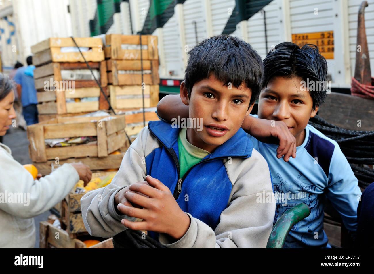Trabajo infantil, dos chicos de 11 y 12 años, trabajando como operadores en el Mercado de Frutas en el mercado de Foto de stock