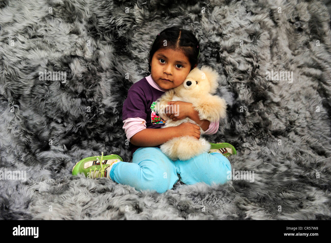 Chica con rasgos indígenas abrazando a un oso de peluche, la producción de juguetes blandos y alfombras de piel Foto de stock