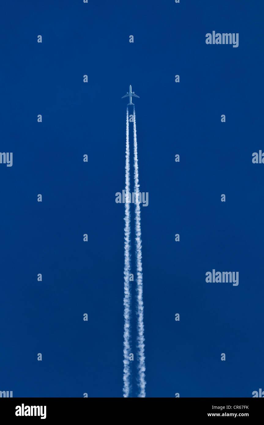 Avión con el doble de las estelas de condensación en el cielo azul Imagen De Stock