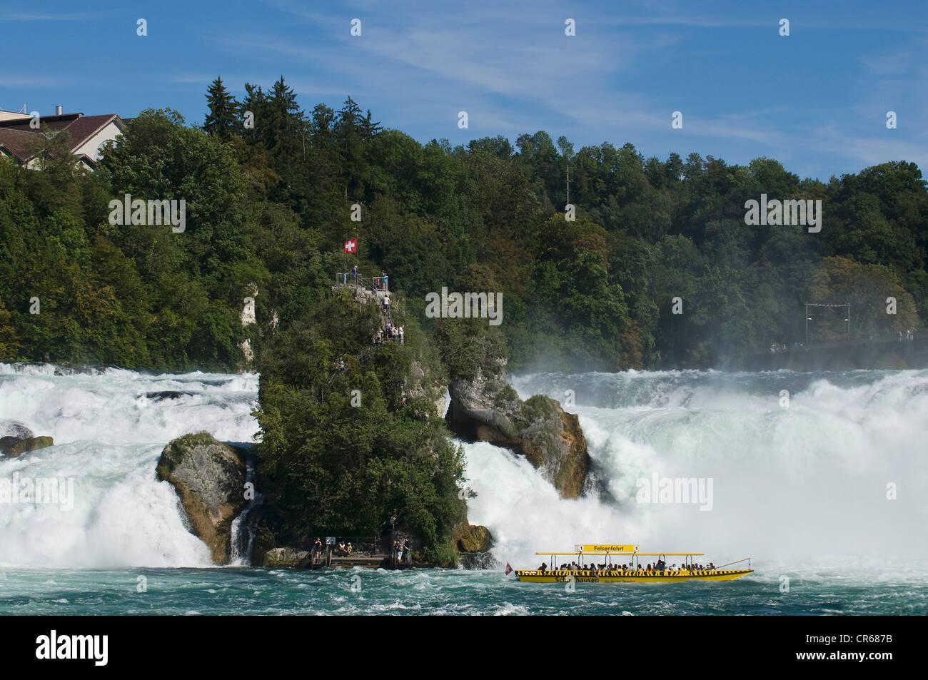 Rock en medio de las rugientes aguas del Rin cae de Schaffhausen, barco de excursión turística en la parte Imagen De Stock