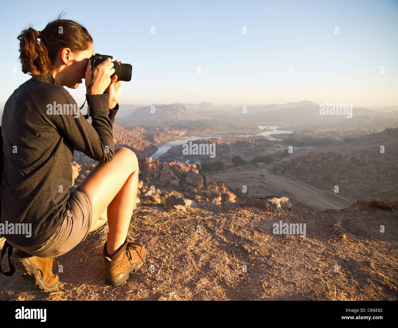 La India, Karnataka, jóvenes mujeres turistas fotografiando en la cima de la colina en Hampi Foto de stock