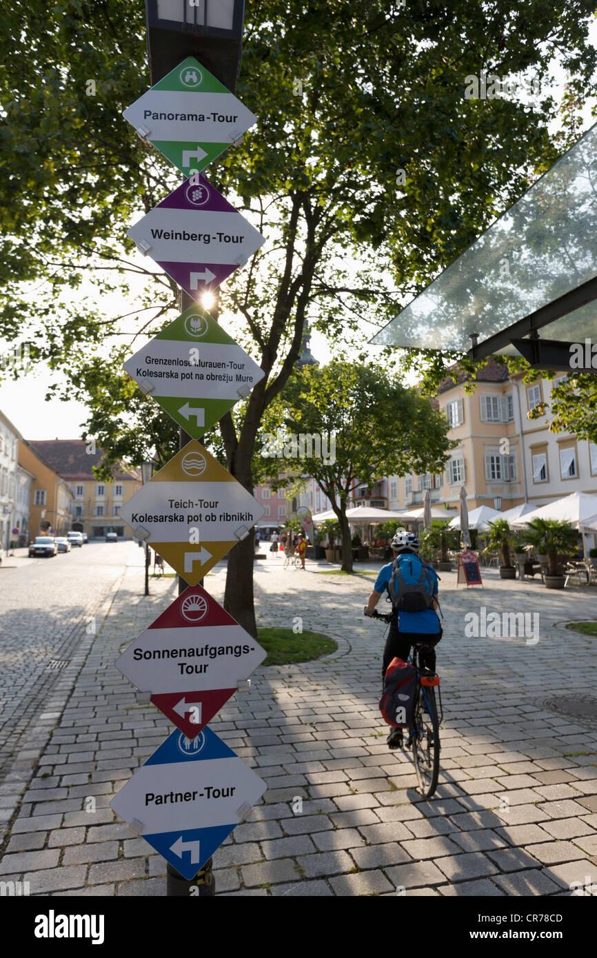 Austria, Estiria, Bad Radkersburg, hombre maduro, montando bicicleta con el cartel con el nombre de la calle Foto de stock