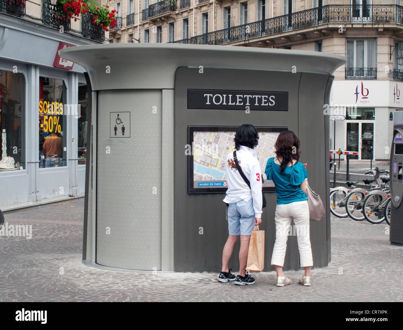 Francia, Paris, aseos públicos y pareja de turistas mirando un mapa del distrito de Les Halles. Imagen De Stock