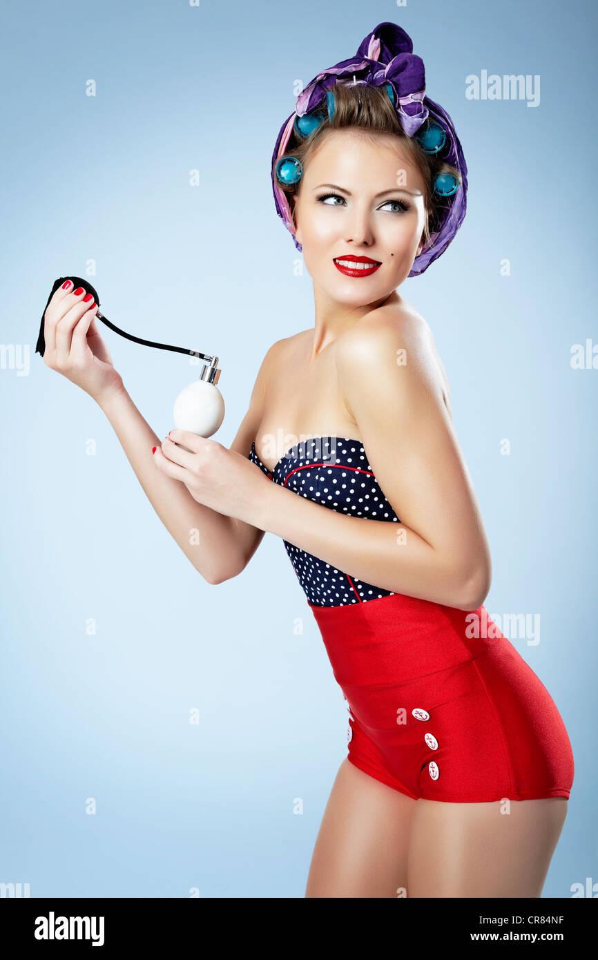 Mujer joven con rizadores de pelo, hot pants y un frasco de perfume, pin-up Imagen De Stock