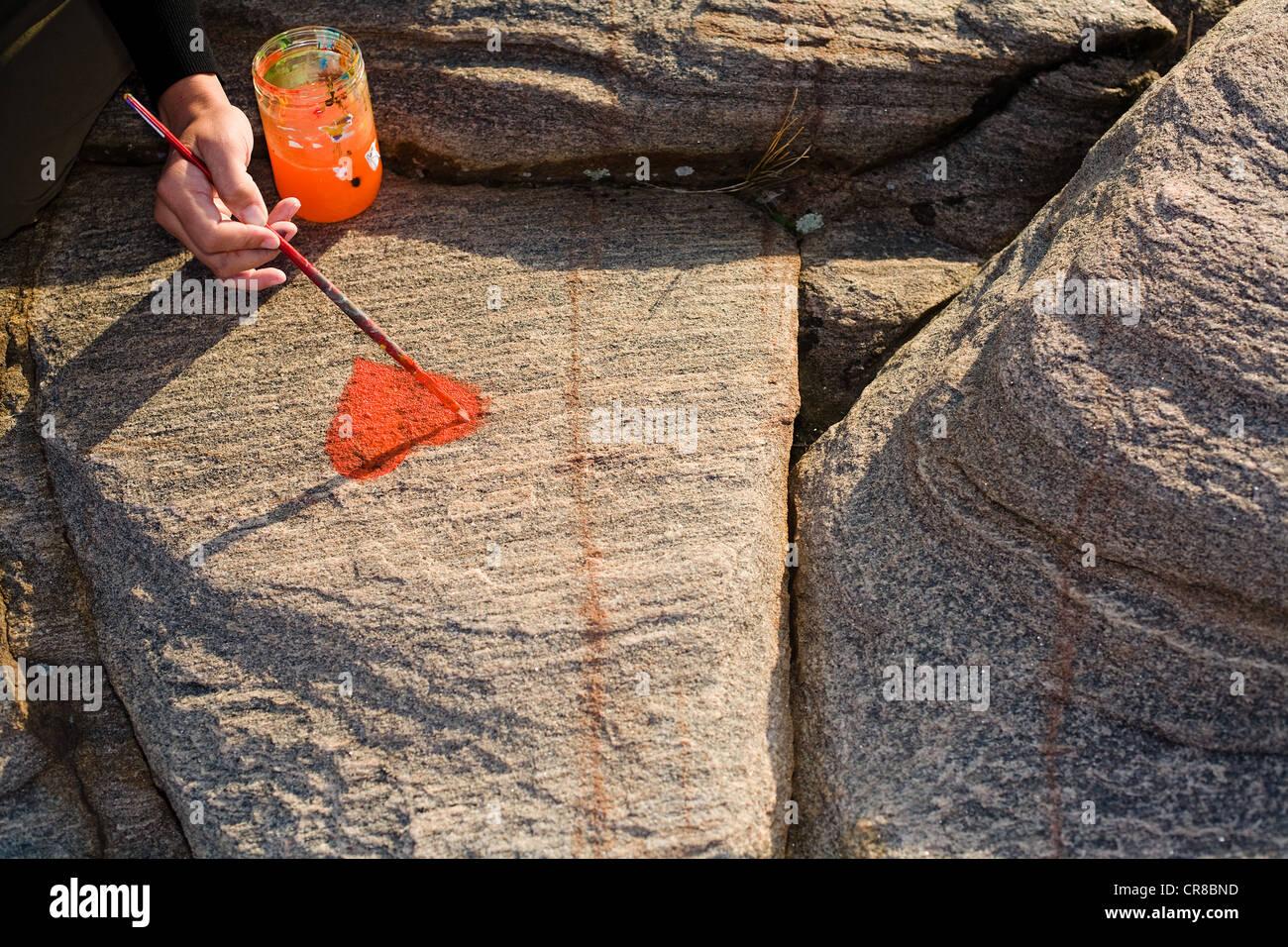 Persona pintando corazón en roca Imagen De Stock