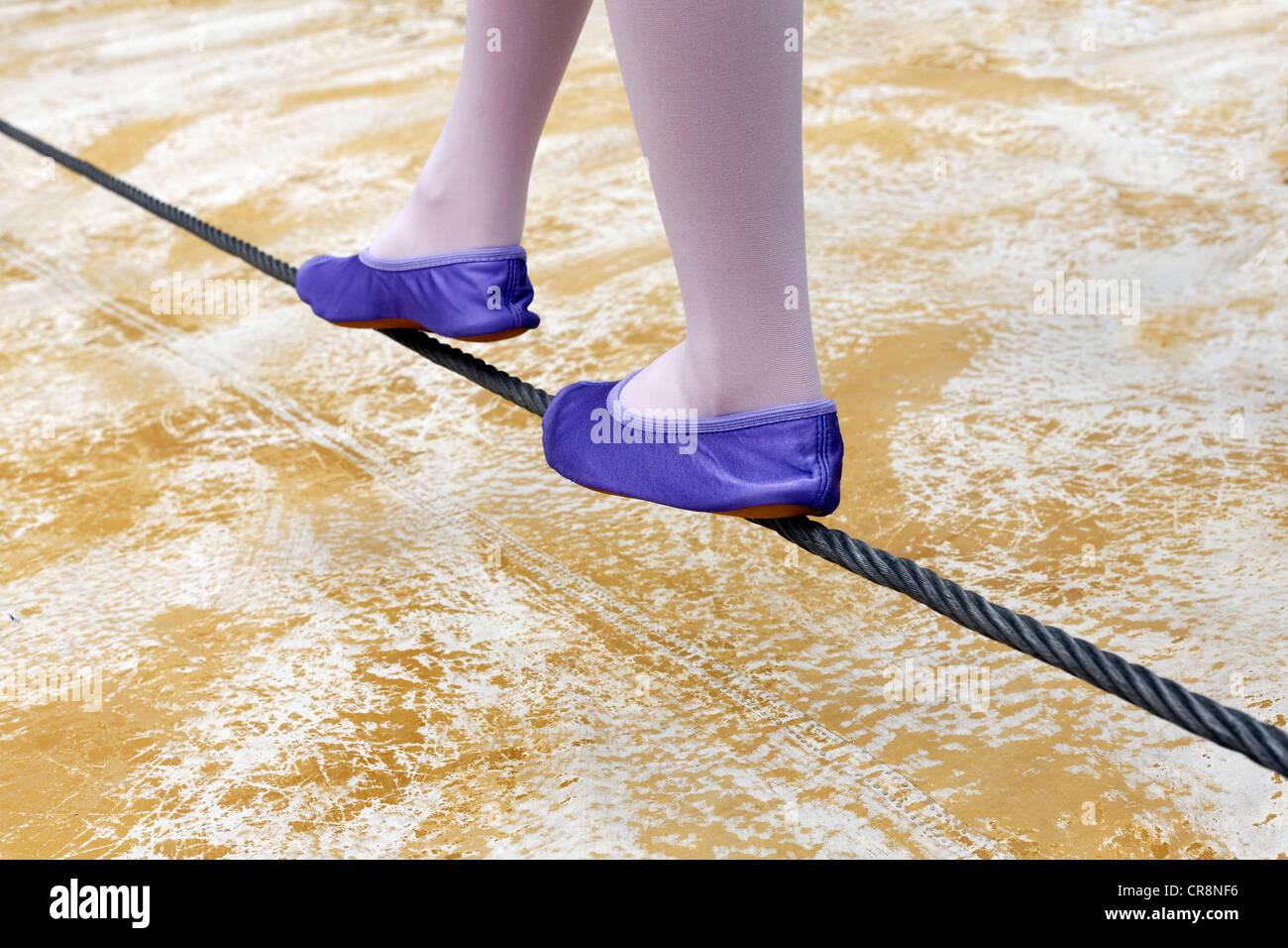 Niña zapatos de ballet en equilibrio sobre un cable de acero, justo por encima del suelo Foto de stock