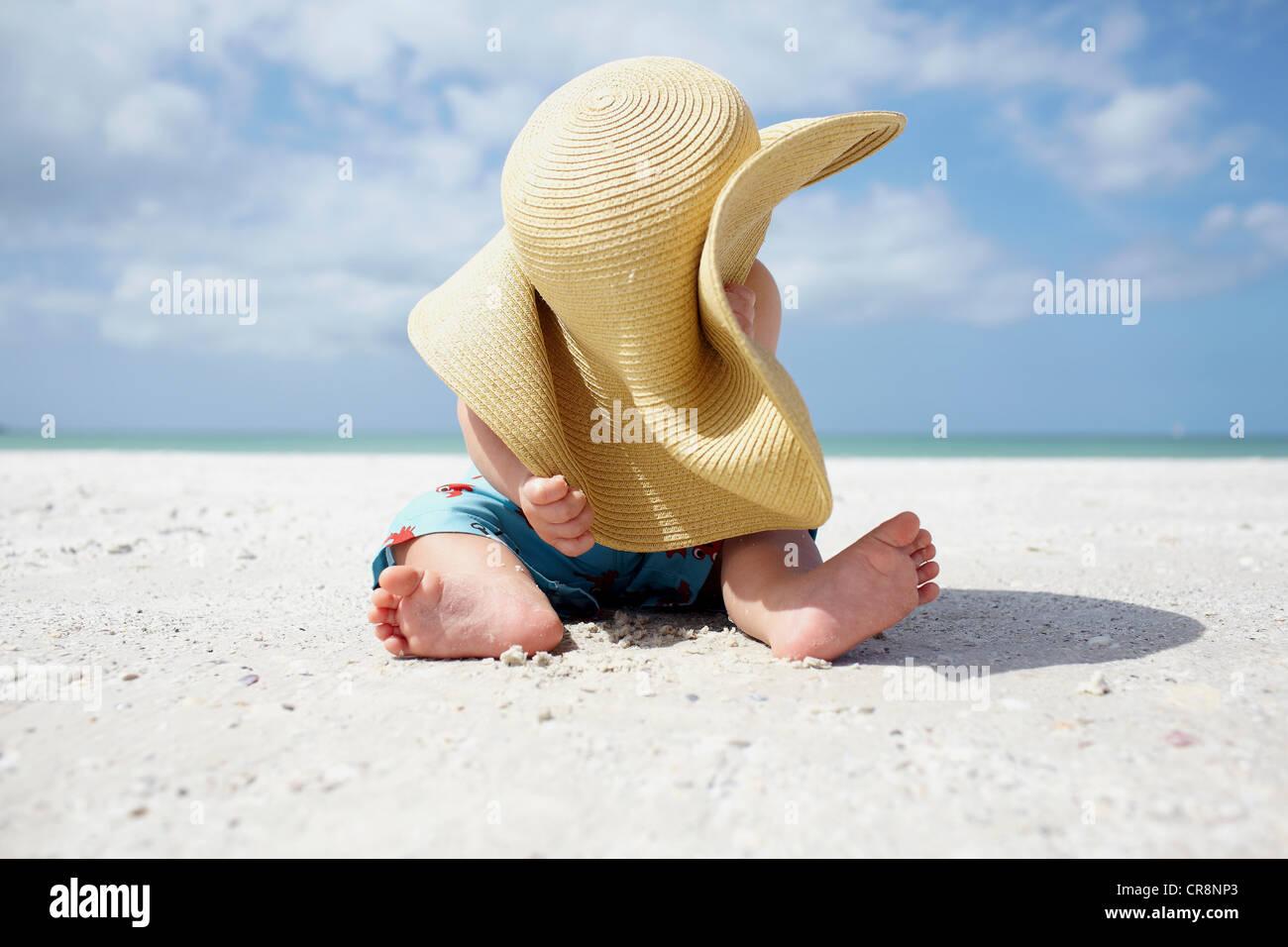 Baby Boy jugando con la madre sombrero para el sol en la playa Foto de stock