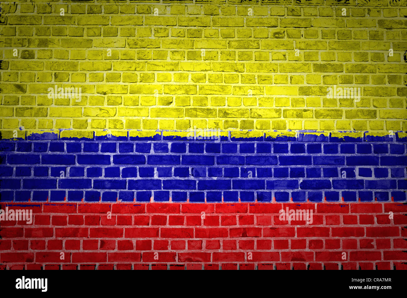 Una imagen de la bandera colombiana pintada sobre una pared de ladrillos en una ubicación urbana Imagen De Stock