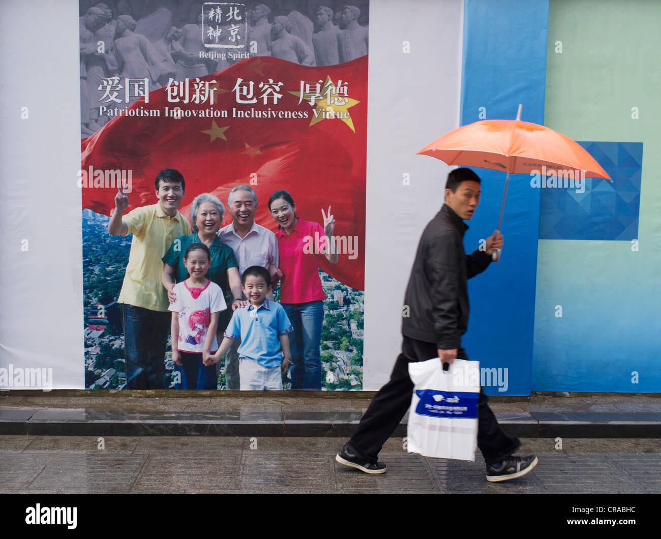 Hombre caminando pasado cartel de propaganda patriótica en Pekín, China Imagen De Stock