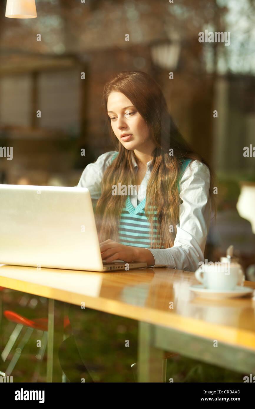 Un estudiante con una laptop sentado en un café, visto a través de una ventana Imagen De Stock