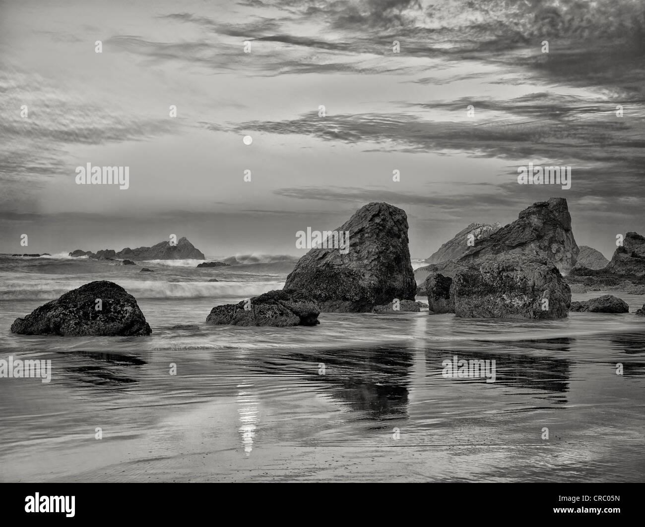 Amanecer y plena moonset con reflexión en Harris Beach State Park, Oregón Imagen De Stock