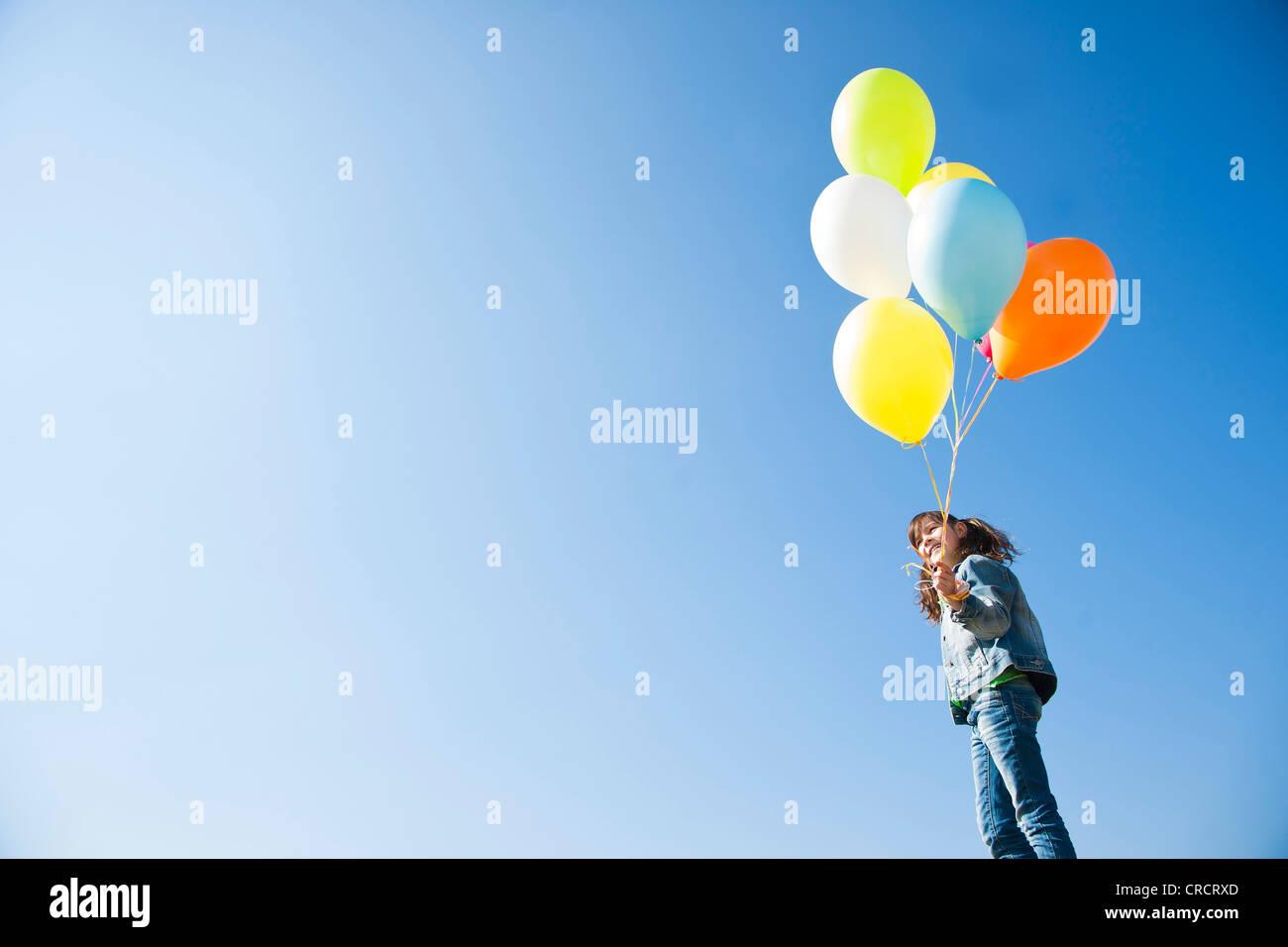 Chica con globos permanente bajo un cielo azul Imagen De Stock