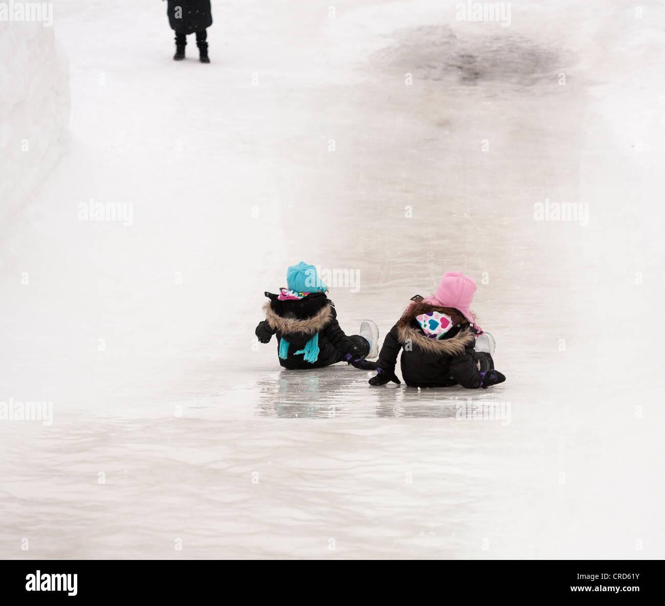 La madre espera: dos niñas se deslice hacia abajo un ice slide. Parte de las instalaciones en el Reino de copo Imagen De Stock
