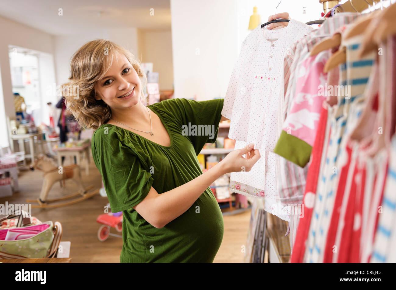 d8f4ce1115 Mujer embarazada comprando ropa de bebé Foto   Imagen De Stock ...
